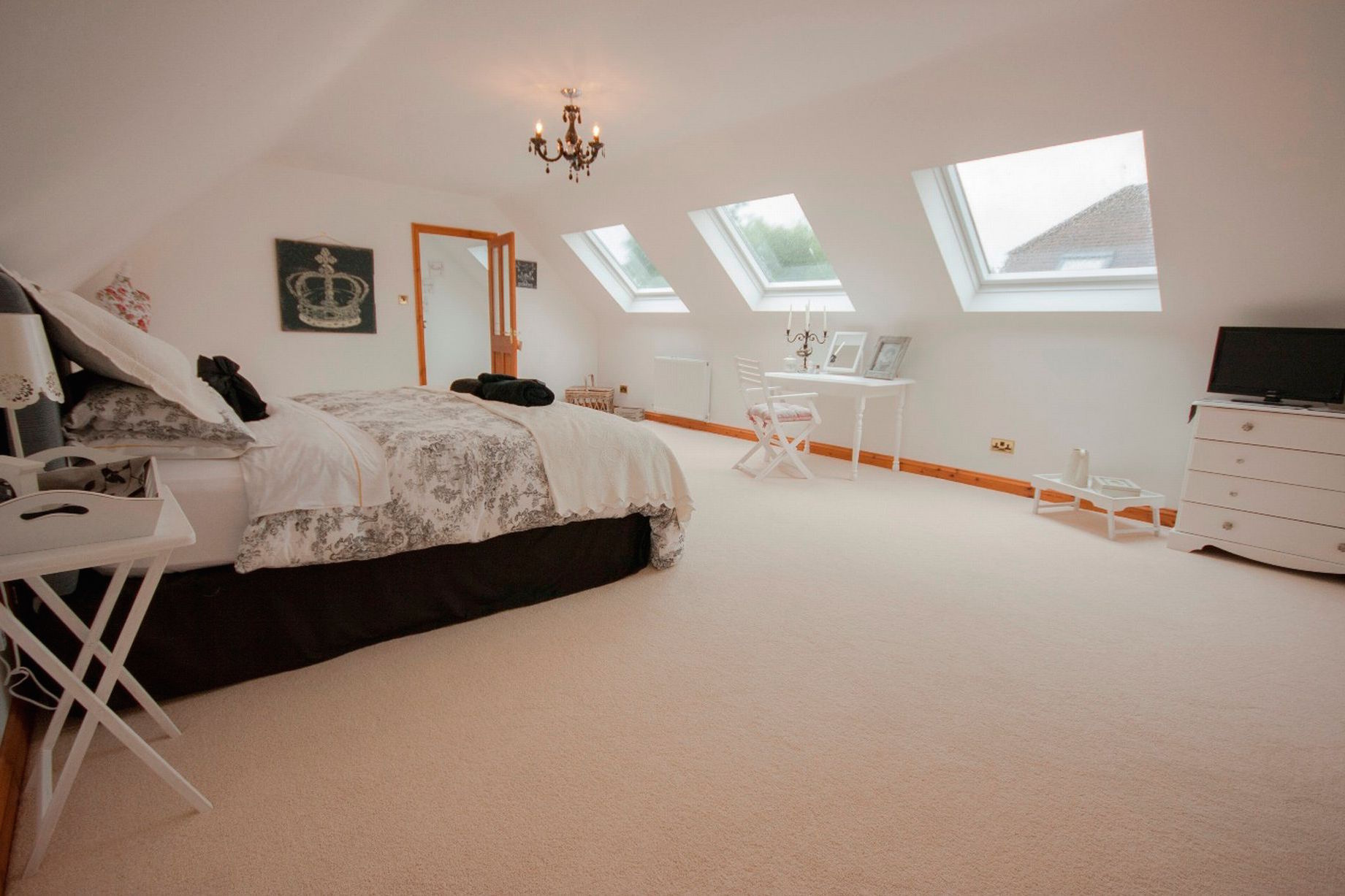 Cottage dormer loft conversion in Orrell, creating a large bedroom with Velux windows